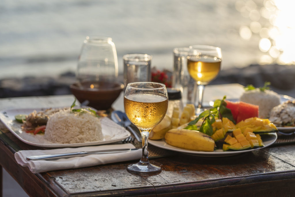 Plates of food and glasses of wine on a beachfront table at sunset.